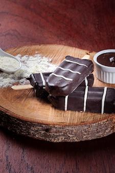 チョコレートで覆われたアイスクリーム。チョコレートとアイスキャンディーの詰め物。ミルク風味。コピースペース