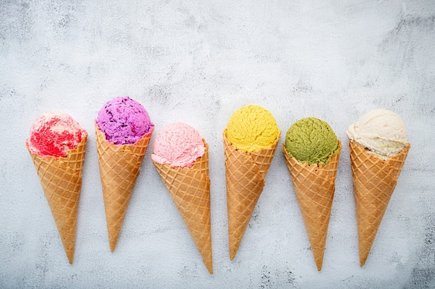 白い石の背景にコーンのアイスクリーム味。夏と甘いメニューのコンセプト。