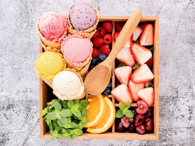 Вкус мороженого в рожках с ягодами в деревянном ящике на бетонном фоне