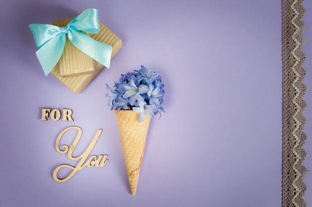 Ice cream horn or cone with purple hyacinth on a purple background with lace.