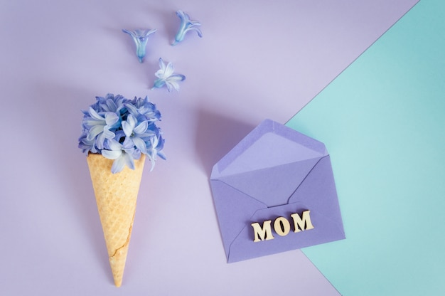 Ice cream horn or cone with purple hyacinth on a purple -mint background.
