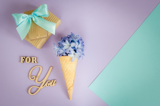 Ice cream horn or cone with purple hyacinth on a purple - mint background.