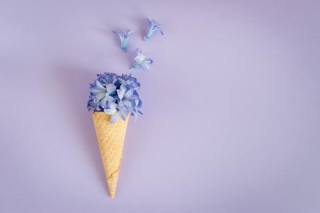 Рожок или конус мороженого с фиолетовым гиацинтом на фиолетовой предпосылке.