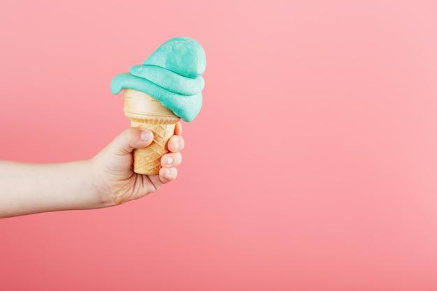 ピンクの背景に子供の手のアイスクリームが溶けます。ブルーアイスクリームのワッフルコーンがとろけます。