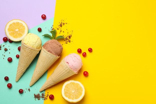 多色の表面にコーン、レモン、クランベリーのアイスクリーム。甘い食べ物