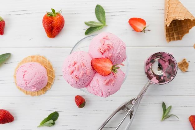 木製のテーブルの上のイチゴとガラスのアイスクリーム