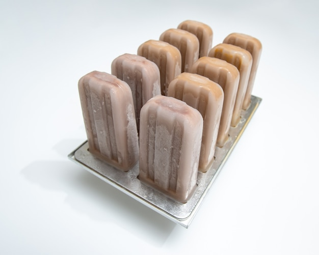テキスト用のスペースと白い背景の上のプラスチック型のアイスクリームロリーコーヒー。夏のデザート