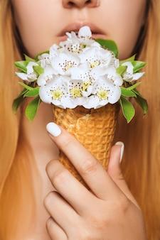 ワッフルコーンの花で作られたアイスクリームは、若い女性が唇の高さで食べて保持しています