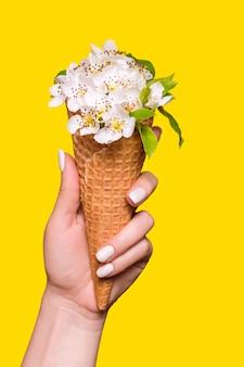 ワッフルコーンの花で作られたアイスクリームは、黄色の背景に若い女性によって保持されます
