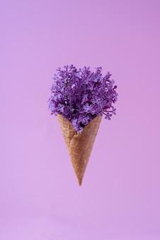 Мороженое из цветов сирени в вафельном стаканчике на фиолетовом фоне