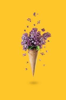 Мороженое из цветов сирени в вафельном рожке на желтом фоне сверху, красивая цветочная композиция. фиолетовые цветы падают или летают в движении. день матери, 8 марта, день святого валентина, день рождения