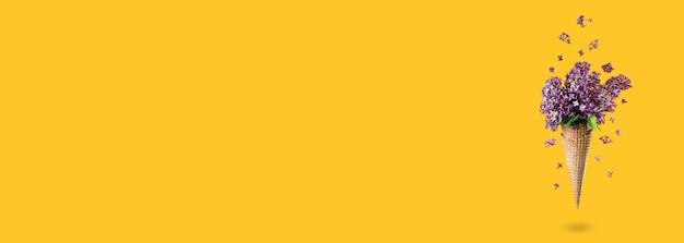 Мороженое из цветов сирени в вафельном рожке на желтом фоне сверху, цветочная композиция. фиолетовые цветы падают или летают в движении. день матери, день святого валентина, день рождения. длинный широкий баннер