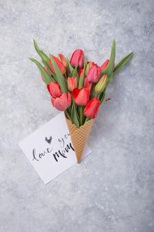 カードとワッフルコーンに赤いチューリップの花のアイスクリームフラットレイアウトスタイルのコンクリートテーブルトップビューでママを愛してください。