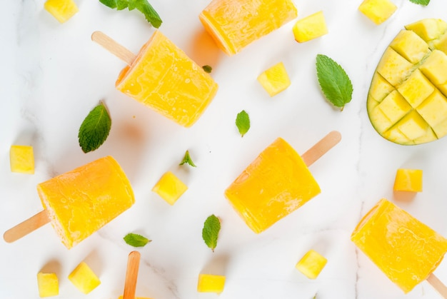 Ice cream, popsicles. organic dietary foods, desserts. frozen mango smoothie, with mint leaves and fresh mango fruit, on a white marble table. copyspace top view