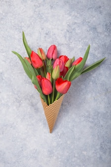 Ice cream of red  tulip flowers in waffle cone  on concrete  table top view in flat lay style.