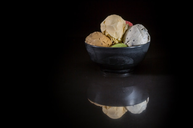 Ice cream scoops in bowl, mixed ice cream in ice cream cup on black background