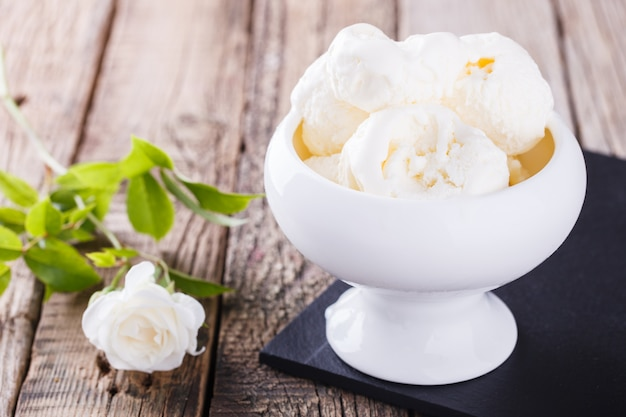 Ice cream scoops in a bowl near a white rose