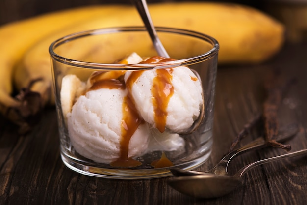 Ice cream scoops with banana slices and caramel sauce