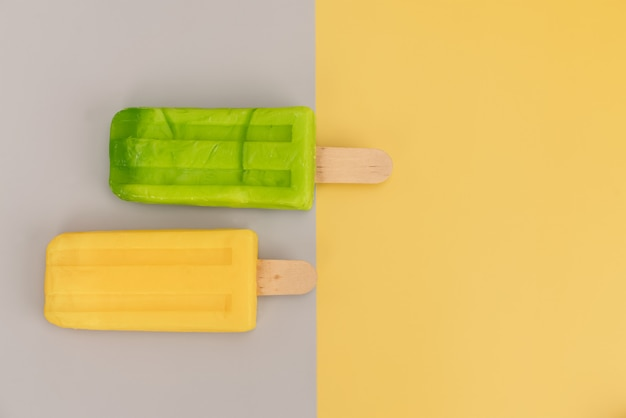 Ice cream stick on gray and yellow background.