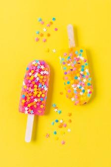 Gelato sul bastone con caramelle sul tavolo