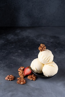 Ice cream three scoops with strawberries and walnuts on a dark background