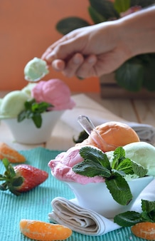 Ice cream of various flavors, accompanied by mint, tangerine and strawberries