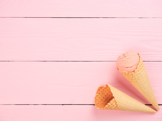 Ice cream waffle cone on a pink background top view copy space summer vacation concept