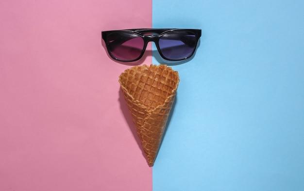 冰淇淋华夫筒和太阳镜在粉红色和蓝色明亮柔和的背景与深阴影,俯视图。平铺夏季构图
