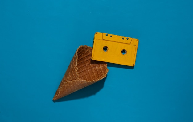 Ice cream waffle cone with audio cassette on blue bright background with deep shadow, top view. flat lay 80s