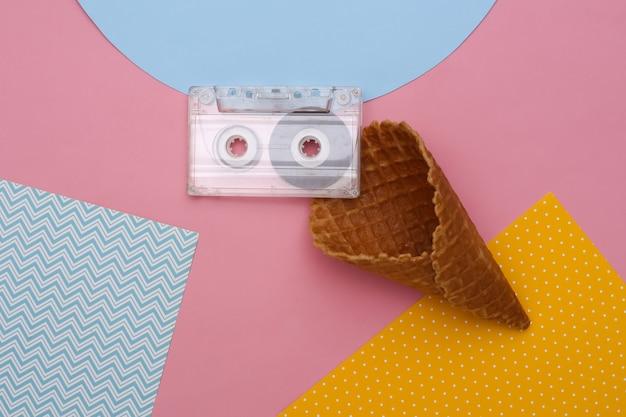 色付きの背景、上面図にオーディオカセットとアイスクリームワッフルコーン。フラットレイ80年代