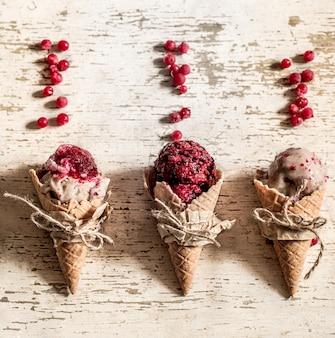 Вафельный рожок мороженого с ягодами на деревянном фоне