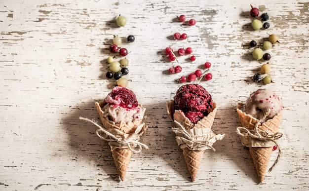 Ice cream waffle cone with berries on wooden table