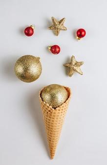 白い背景の上のクリスマスつまらないものとアイスクリームワッフルコーン。上面図。フラットレイ