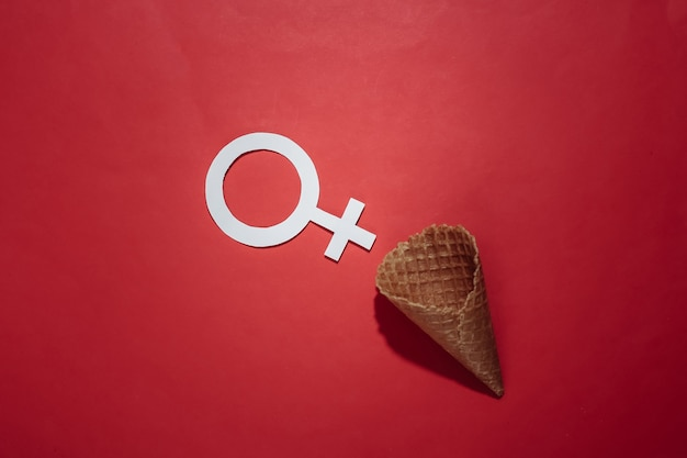 Ice cream waffle cone with  female gender symbol on red bright background. top view