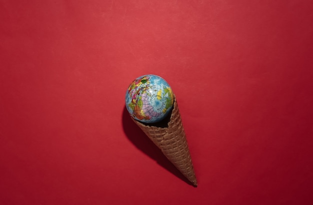 Ice cream waffle cone with globe on red bright background. top view