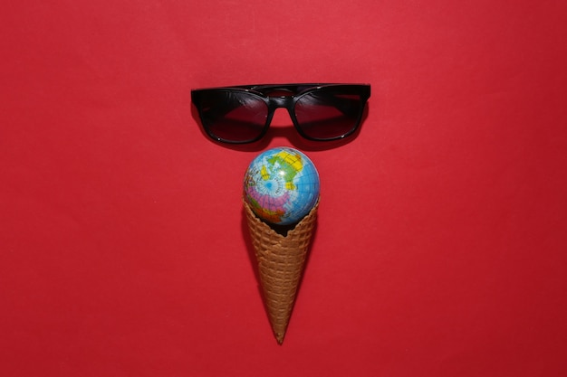 Ice cream waffle cone with globe, sunglasses on red bright background.