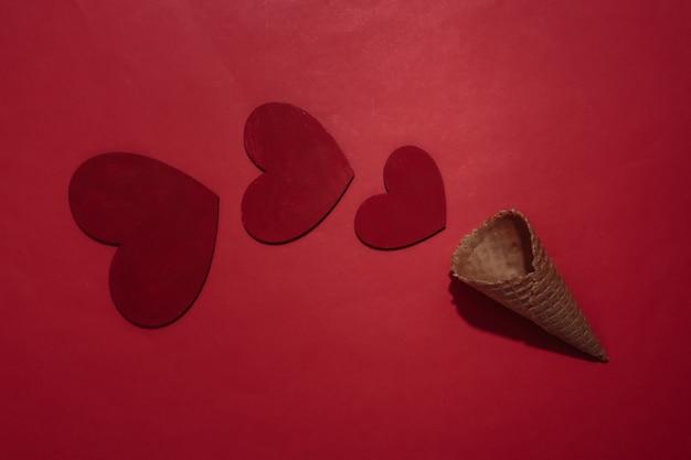 赤く明るい背景にhesrtsとアイスクリームワッフルコーン。ロマンチックなフラットレイ。上面図