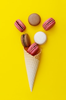 Ice cream waffle cone with macaroons on yellow background. flat lay, dessert.