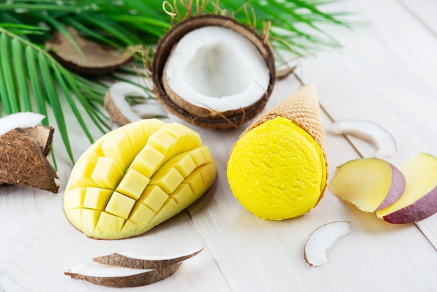 Ice cream in a waffle cone with mango and coconut on a wooden table