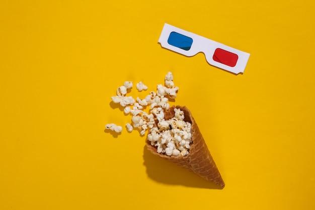 ポップコーンとアイスクリームワッフルコーン、深い影、上面図と明るい黄色の背景に3dメガネ。フラットレイ最小組成