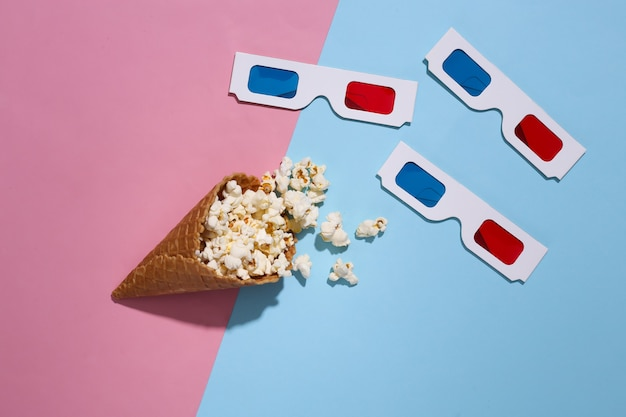 Ice cream waffle cone with popcorn, 3d glasses on pink and blue bright pastel background with deep shadow, top view. movie time. flat lay minimal composition