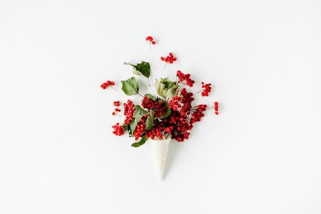 Вафельный рожок мороженого с букетом красной рябины на белом