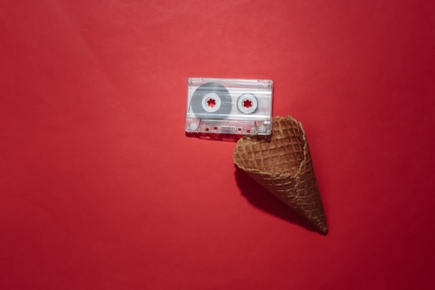 Ice cream waffle cone with retro audio cassette on red bright background. top view