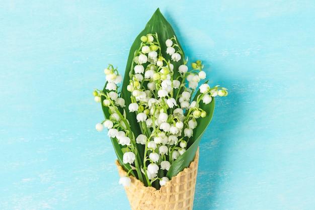 青の背景に春のスズランの花とアイスクリームワッフルコーン。最小限の春のコンセプト。フラットレイ