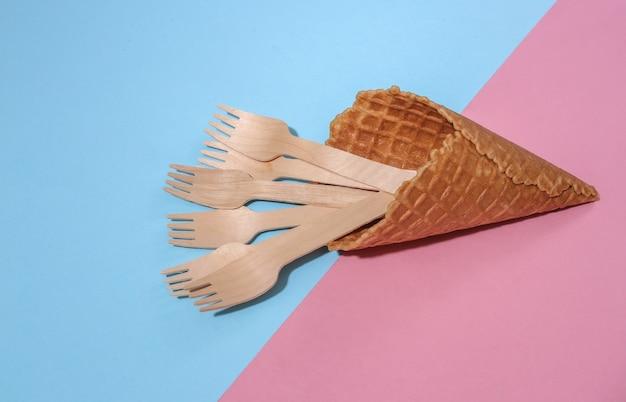 Вафельный рожок мороженого с деревянными вилками на розовом и синем ярком пастельном фоне с глубокой тенью, вид сверху. плоская планировка эко-композиции