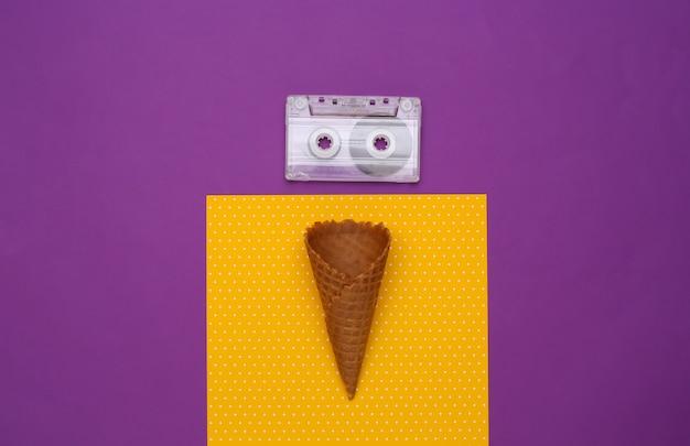紫黄色の背景にアイスクリームワッフルコーンとオーディオカセット。