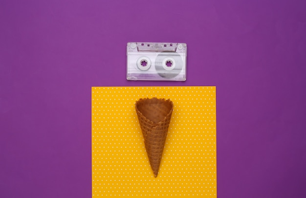 Ice cream waffle cones and audio cassette on purple yellow background.
