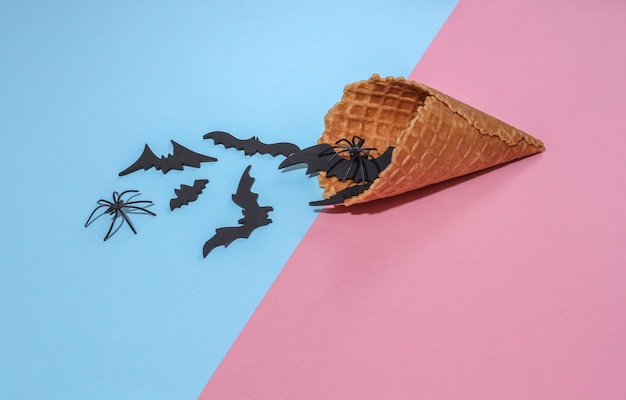 아이스크림 와플 콘에는 장식용 박쥐와 거미가 있는 분홍색과 파란색 밝은 파스텔 배경에 깊은 그림자가 있습니다. 할로윈 구성