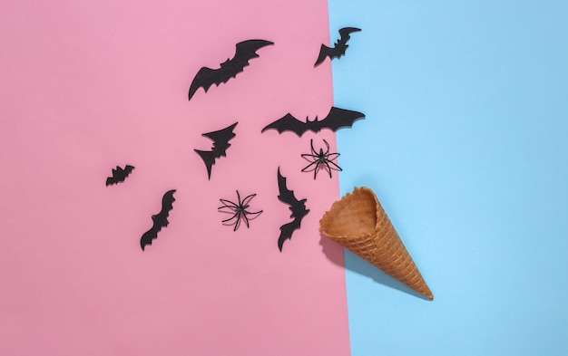 분홍색과 파란색 밝은 파스텔 배경에 장식용 박쥐와 거미가 있는 아이스크림 와플 콘은 깊은 그림자, 위쪽 전망을 제공합니다. 평면 누워 할로윈 구성