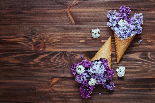 Ice cream waffle cones with lilac flowers on rustic background with copy space
